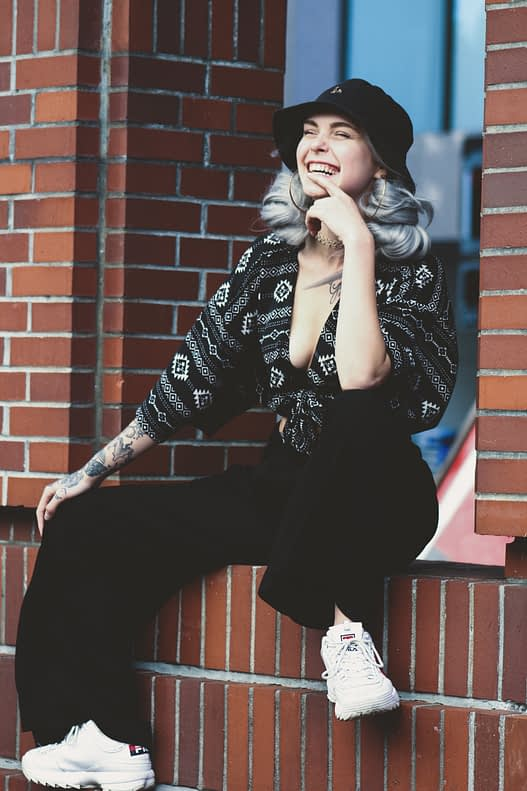 Girl with trendy silver hair wearing a fashionable outfit sits on a brick wall.