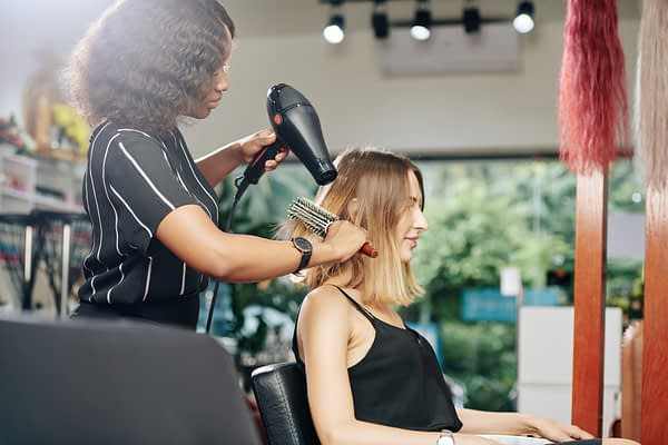 woman styling another woman's hair in a salon