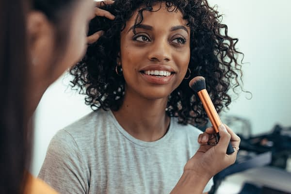 woman having her makeup done by another woman