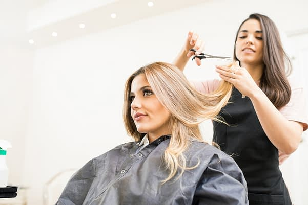 A cosmetology student cuts a woman's hair.