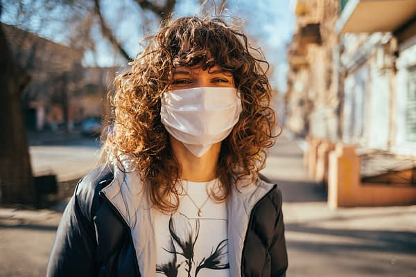 woman wearing face mask and black jacket outside