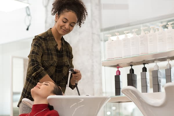 woman washing another woman's hair in a salon