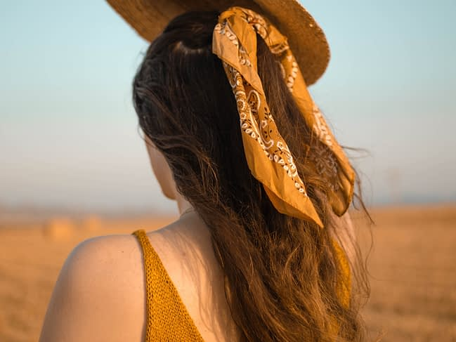 Girl wearing a yellow bandana in her long brown hair.