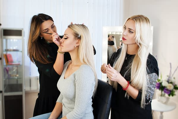 woman instructing another woman on makeup application