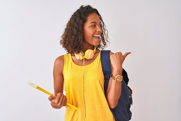 woman in yellow top wearing backpack laughing and pointing over her shoulder