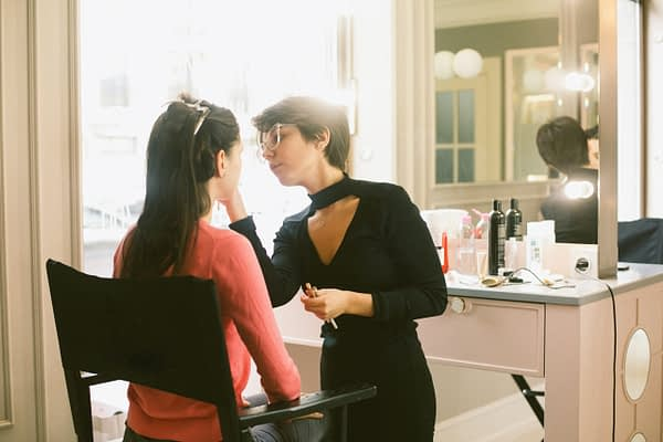 woman doing another woman's makeup in a salon