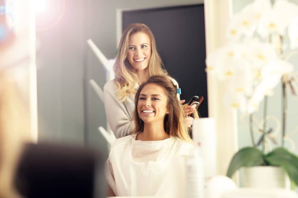 Hairstylist doing woman's hair both are smiling