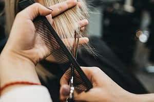 Stylist cutting hair with comb