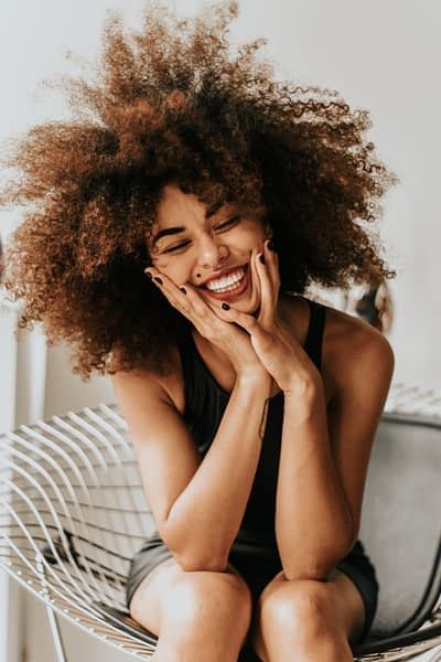 woman with natural curly hair sits in a chair and laughs