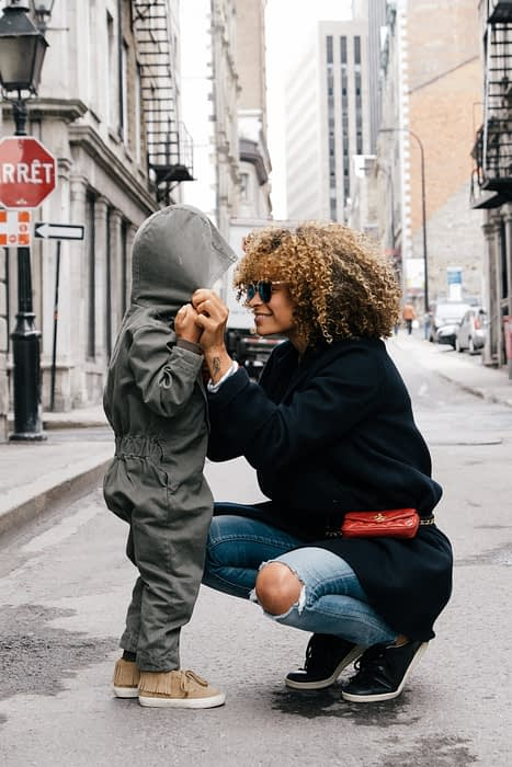 woman smiling and holding looking her toddler in the eye