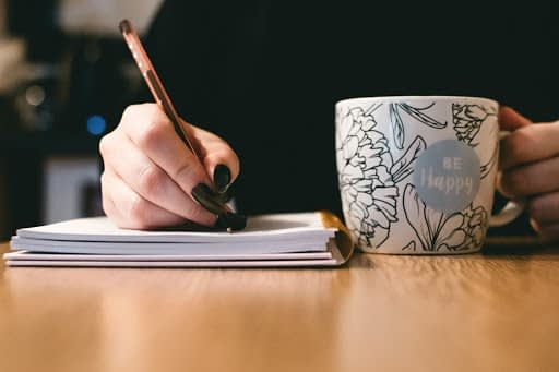 woman with a cup of coffee writing in a notebook