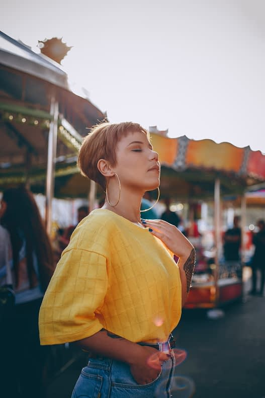 Girl with pixie cut in a yellow top at a carnival.