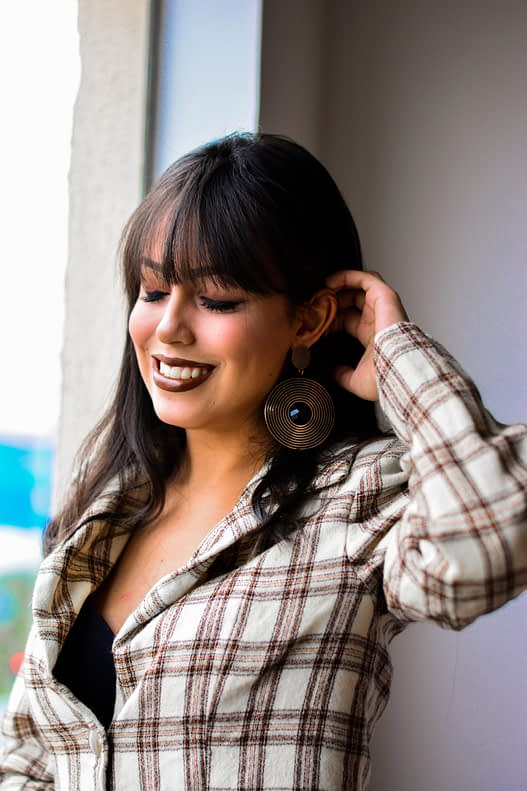 Girl with blunt bangs wearing a plaid jacket.