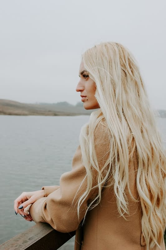 Girl with long blonde hair leaning on a dock on a lake