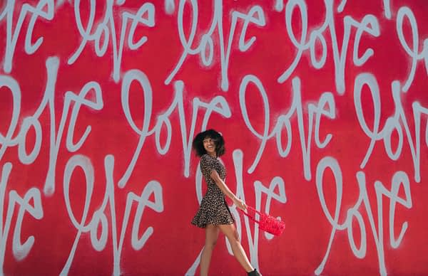 """woman in leopard print dress standing in front of a red wall mural that says """"love"""""""