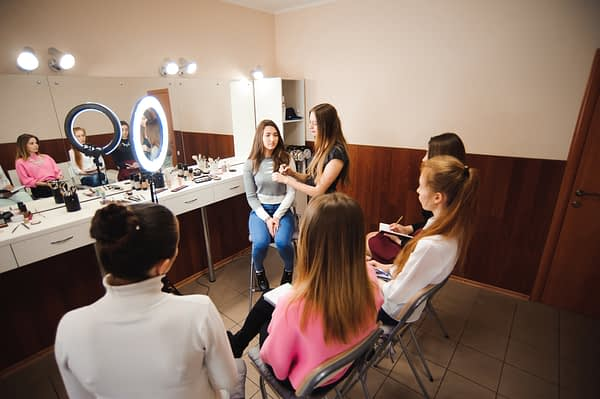 woman instructing students about makeup application