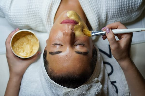 woman getting a face mask at a spa