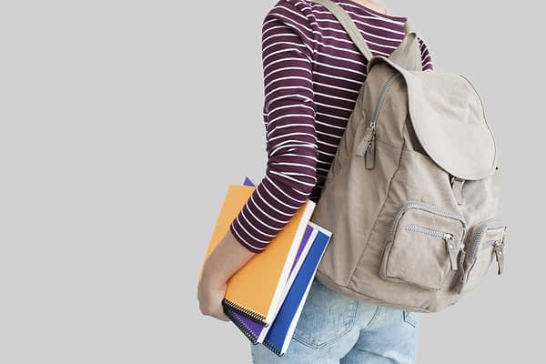 woman wearing backpack holding a stack of notebooks