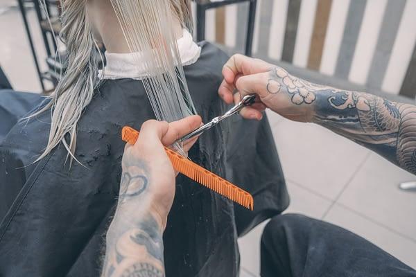 man's hands shown cutting a woman's hair