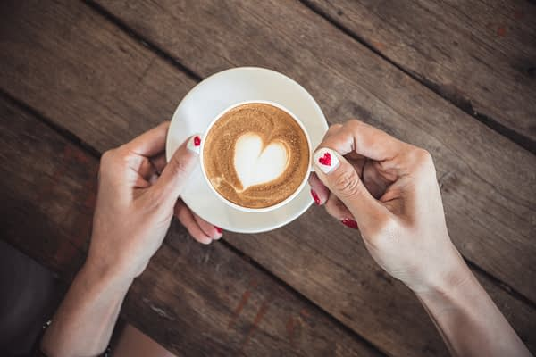 woman's hands with heart painted fingernails holding a cup of coffee