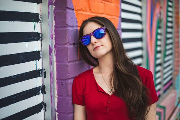 brunette woman wearing sunglasses leaning against a mural