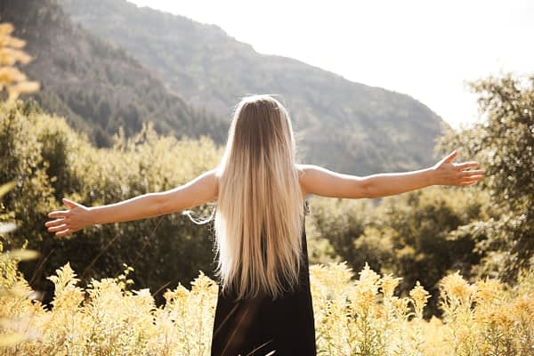 woman with blonde hair holding her arms out on a hike