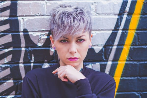 woman with purple hair leaning against a mural