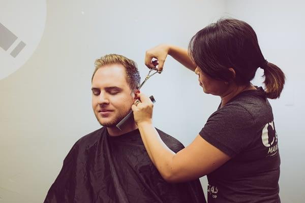 woman styling man's hair