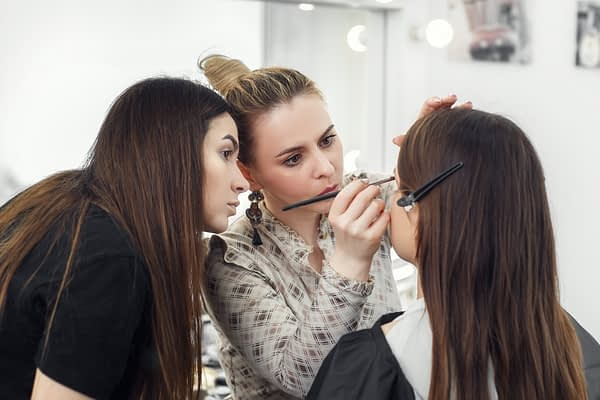 beauty school instructor teaching students how to apply makeup
