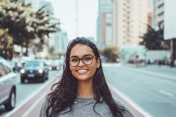 woman wearing glasses standing in a street downtown