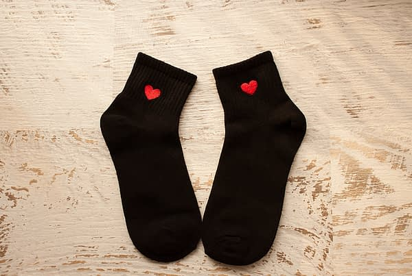 black socks with red hearts laid out on a wood table