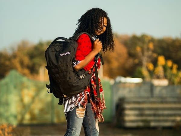 woman walking and wearing a backpack