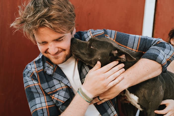 Man in a plaid shirt with messy hair holding a dog.