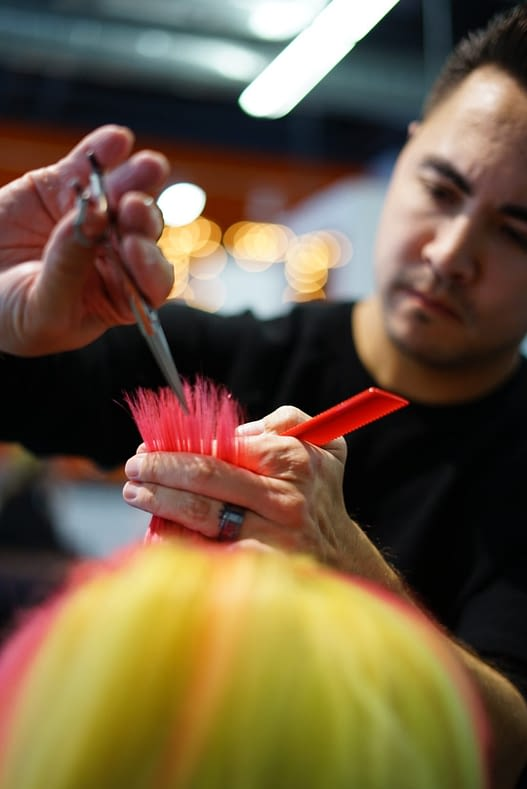 Stylist cutting brightly colored hair.