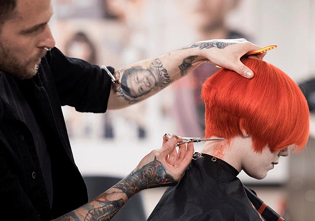 male hair stylist trimming red dyed hair