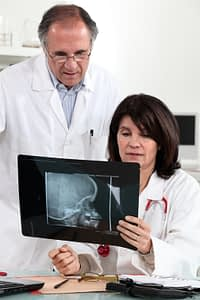 A doctor looking at a brain tumor with his assistant.