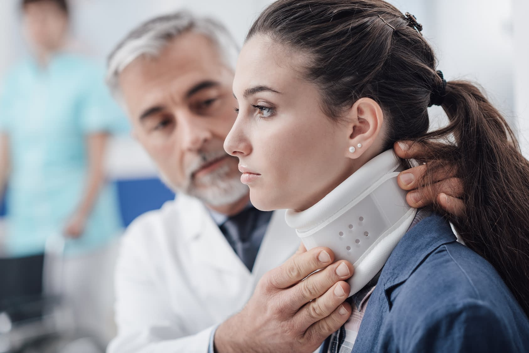 Doctor fitting patient with neck brace