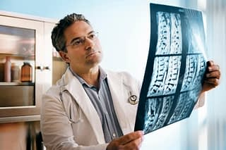 Doctor examines X-rays of spine