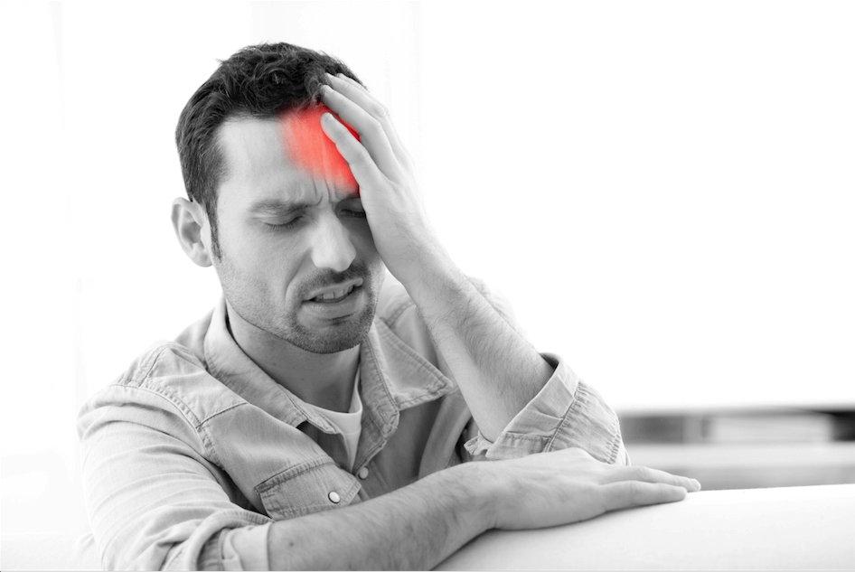 A man holding his face in pain from a serious headache.