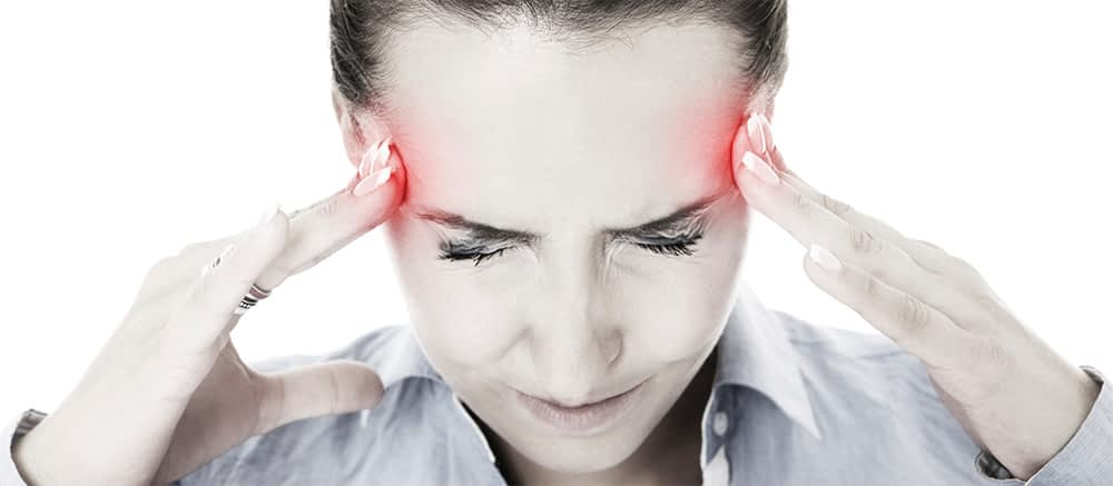 woman with head pain pressing on her temples