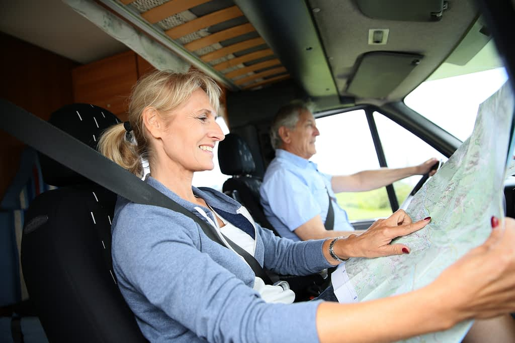 A couple driving with good posture, which can help with back pain.