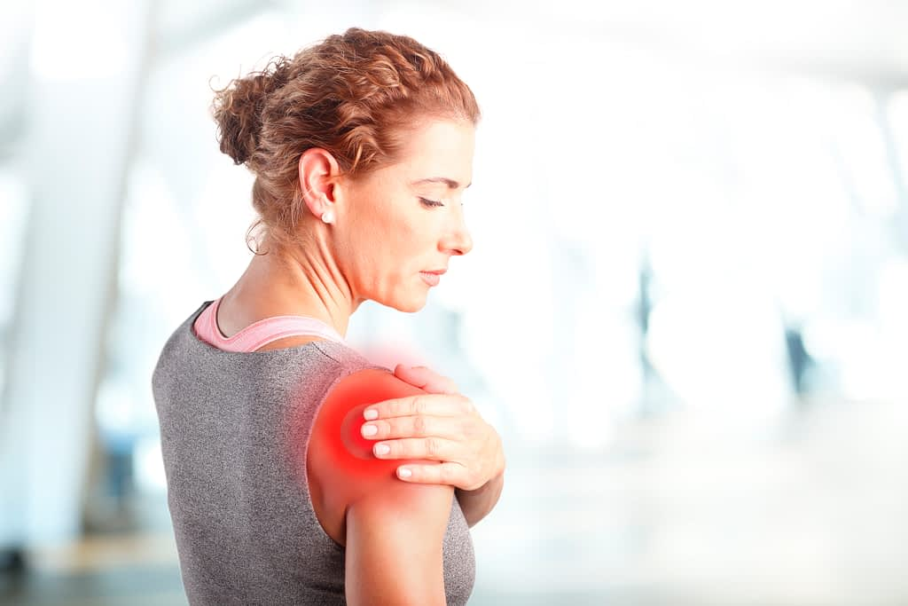 Woman holding pained shoulder experiencing bone cyst