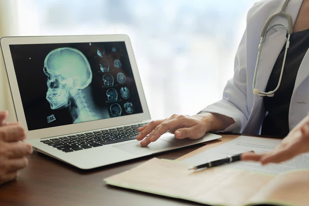 Laptop displaying hydrocephalus next to doctor talking to patient