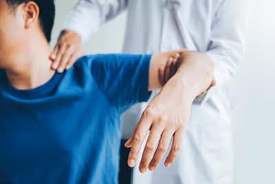 Doctor Examines Patient Shoulder