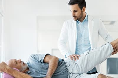 Doctor Examines Senior Man's Hip