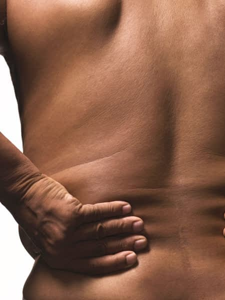 A man holding the lower left side of his back from pain.
