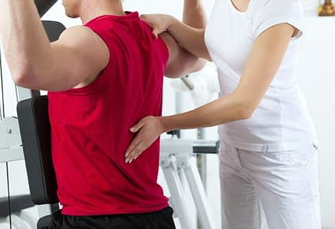 Specialist press hand to patient's spine during workout