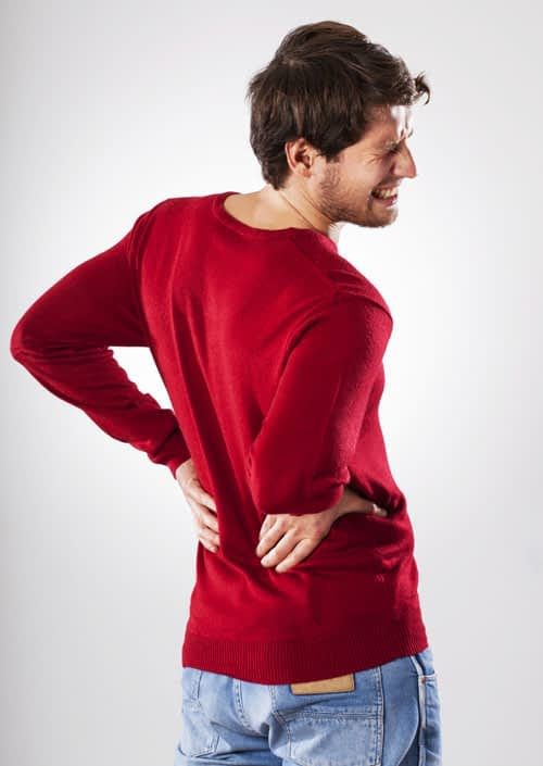 Man wincing in pain from herniated disc in back