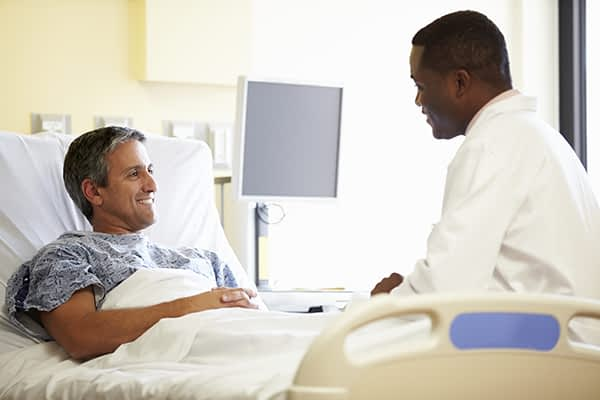 A doctor sitting with his patient before he undergoes spinal surgery.