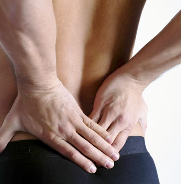 Man pressing both hands to lower back